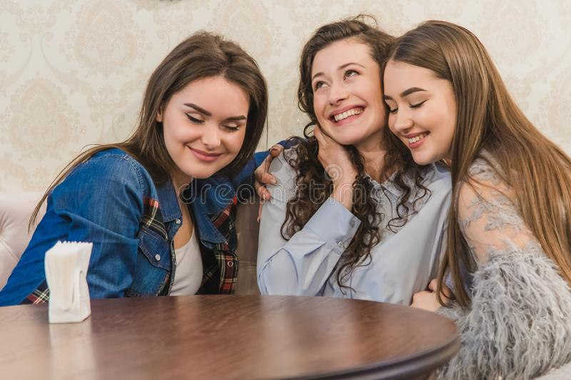 Three young women sitting together in small cafes against large windows and embracing each other. Beautiful young girls. Drinking coffee. At a meeting in the royalty free stock images