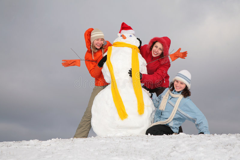Three young women and snowman 2 royalty free stock photography