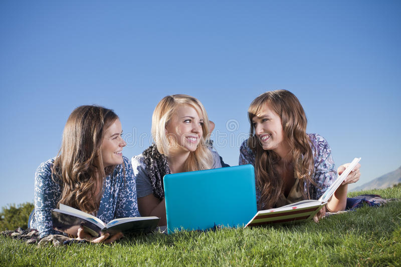 Three Young women studying in the outdoors. Three young attractive women reading and studying together outdoors stock photos