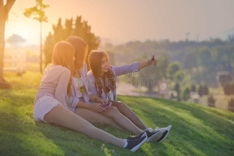 Three young women taking selfie with mobile phone. Swag teen girls. Outdoor lifestyle portrait royalty free stock images