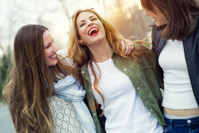 Three young women talking and laughing in the street. stock photography