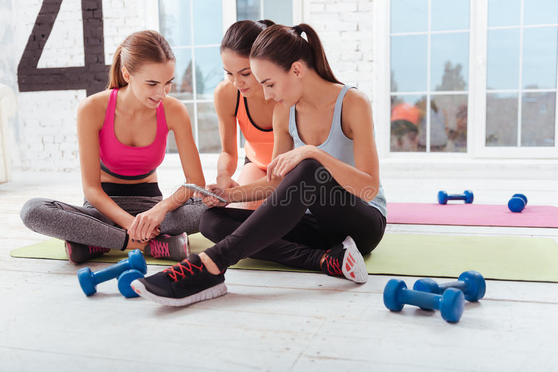 Three young women using smartphone in a gym stock photography