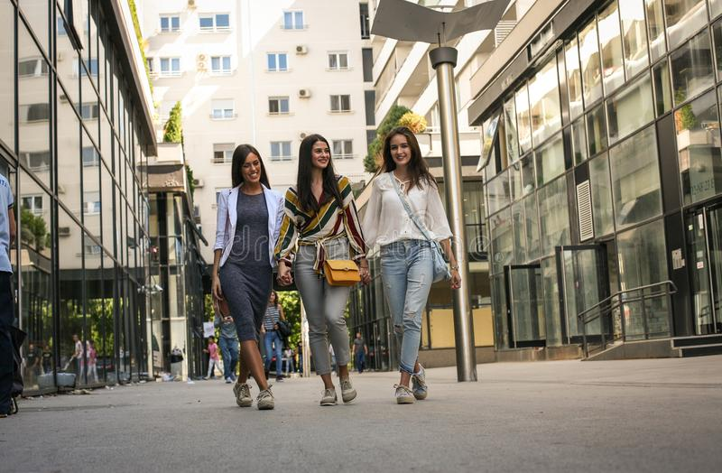 Three young women walking street, holding hands. stock photos