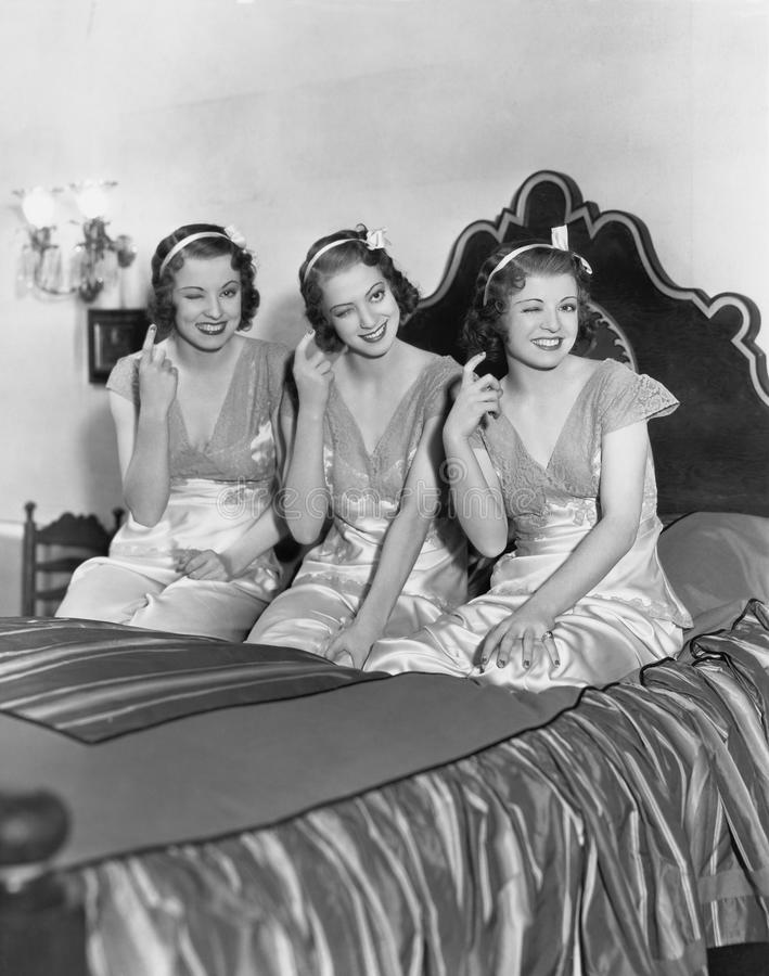 Three young women winking royalty free stock images