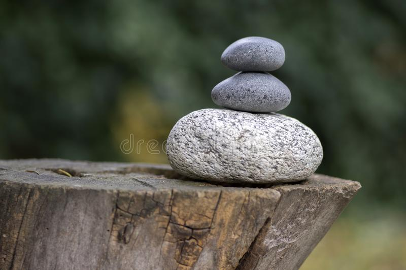 Three zen stones pile on wooden stump, white and grey meditation pebbles tower royalty free stock image