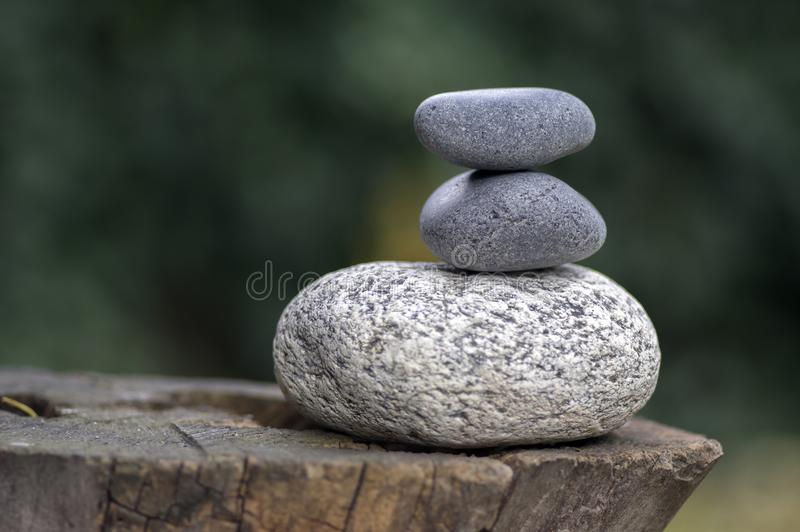 Three zen stones pile on wooden stump, white and grey meditation pebbles tower royalty free stock photo