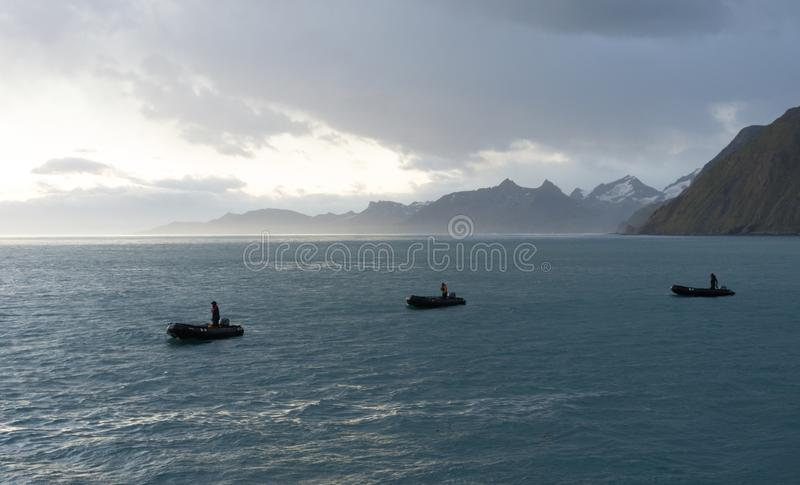Three Zodiaks with Drivers at Sunrise stock image