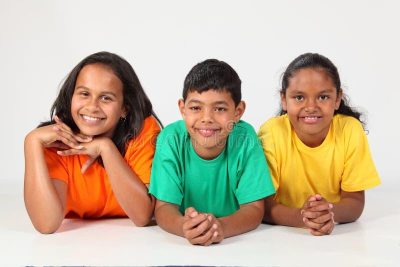 Threesome de los amigos felices de la escuela que mienten en suelo imagen de archivo