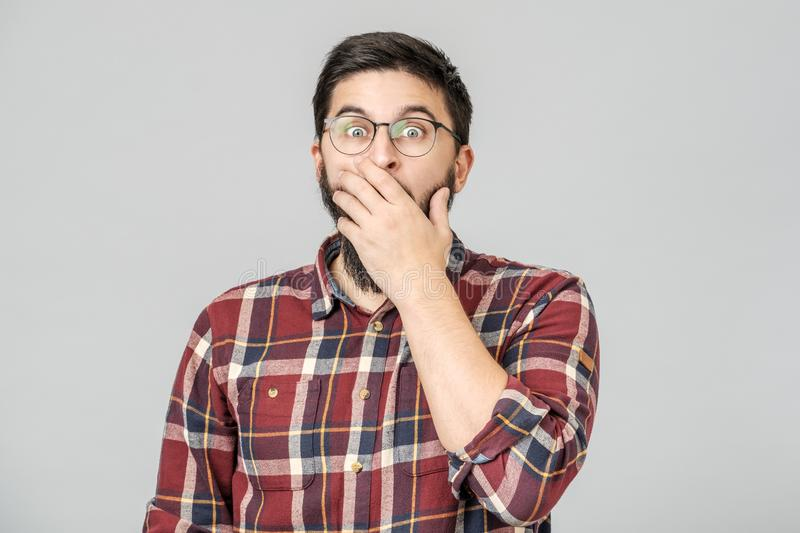 Thrilled excited guy in glasses isolated over gray royalty free stock photography