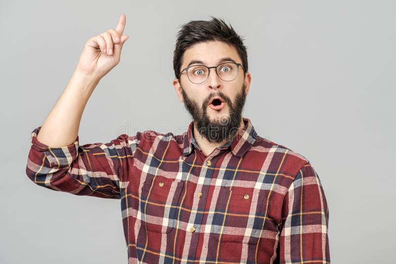 Thrilled excited guy in glasses isolated over gray stock photography