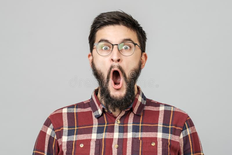 Thrilled excited guy in glasses isolated over gray royalty free stock image