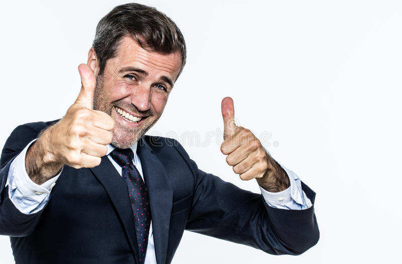 Thrilled smart young businessman with thumbs up approving corporate wellbeing. And management with elegance, copy space, white background stock photos