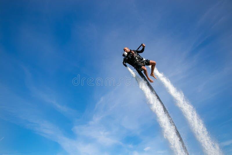 Thrillseeker,运动员被束缚喷射列弗,升空腾飞入与whispy云彩的蓝天 免版税库存图片