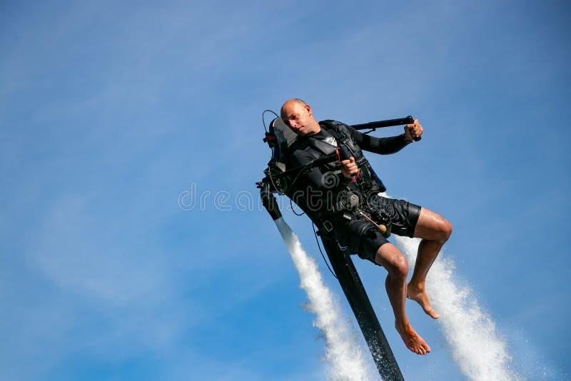 Thrillseeker, atleta prendido com correias a Jet Lev, levitação sobe em um céu azul com nuvens whispy foto de stock