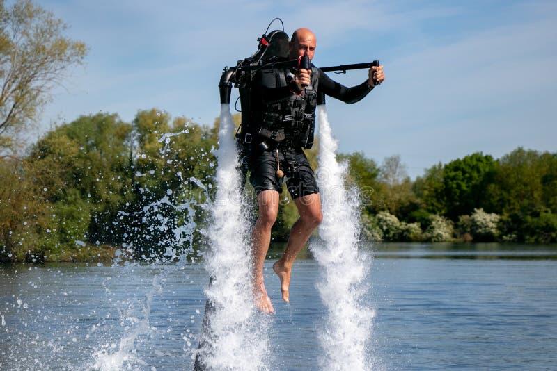 Thrillseeker, sport acquatici amante, atleta attaccato a Jet Lev, levitazione sorvola il lago con cielo blu e gli alberi immagini stock libere da diritti