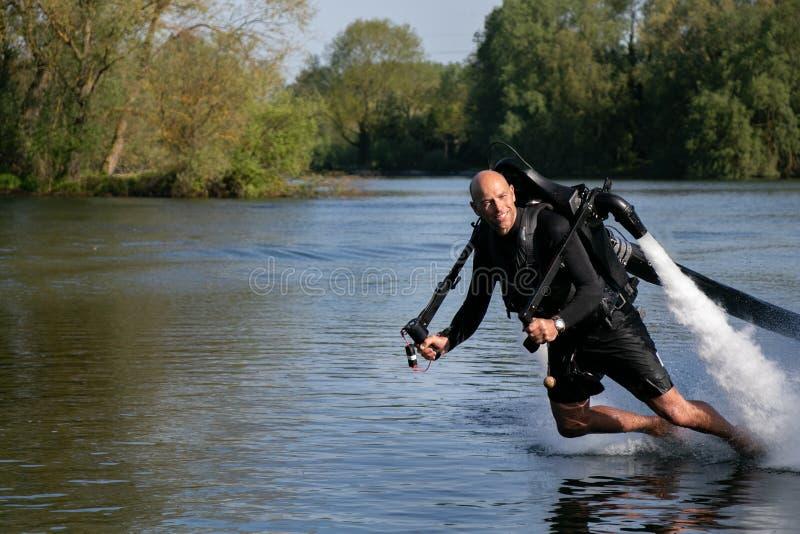 Thrillseeker vattensportar vännen, idrottsman nen som fästas till Jet Lev, svävning svävar över sjön med blå himmel och träd arkivfoto