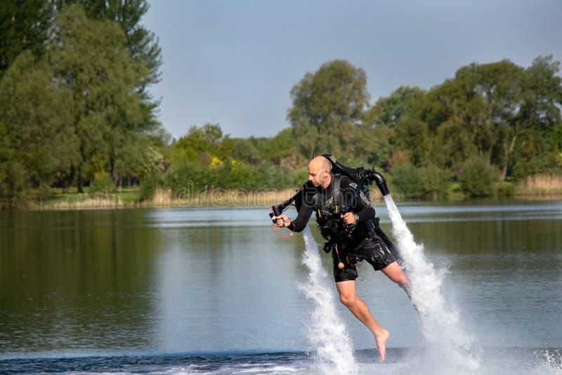 Thrillseeker vattensportar vännen, idrottsman nen som fästas till Jet Lev, svävning svävar över sjön med blå himmel och träd arkivfoton