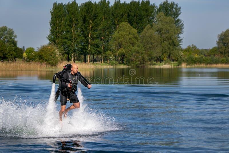 Thrillseeker vattensportar vännen, idrottsman nen som fästas till Jet Lev, svävning svävar över sjön med blå himmel och träd royaltyfria foton