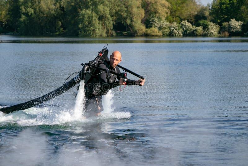 Thrillseeker vattensportar vännen, idrottsman nen som fästas till Jet Lev, svävning svävar över sjön med blå himmel och träd arkivbilder