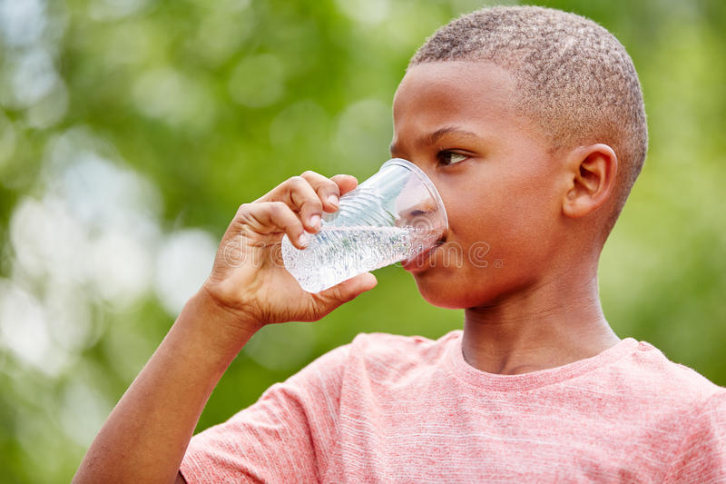 Thristy african boy drinks water stock images