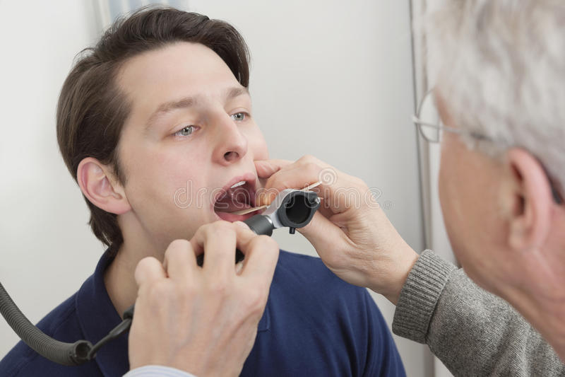 Throat Exam With Depressor. Young man getting his throat checked by male doctor at clinic stock images