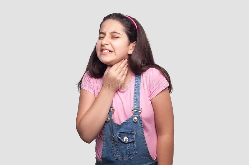 Throat or neck pain. Portrait of sick brunette young girl in pink t-shirt and blue overalls standing and holding her painful neck. And feeling bad. indoor royalty free stock photography