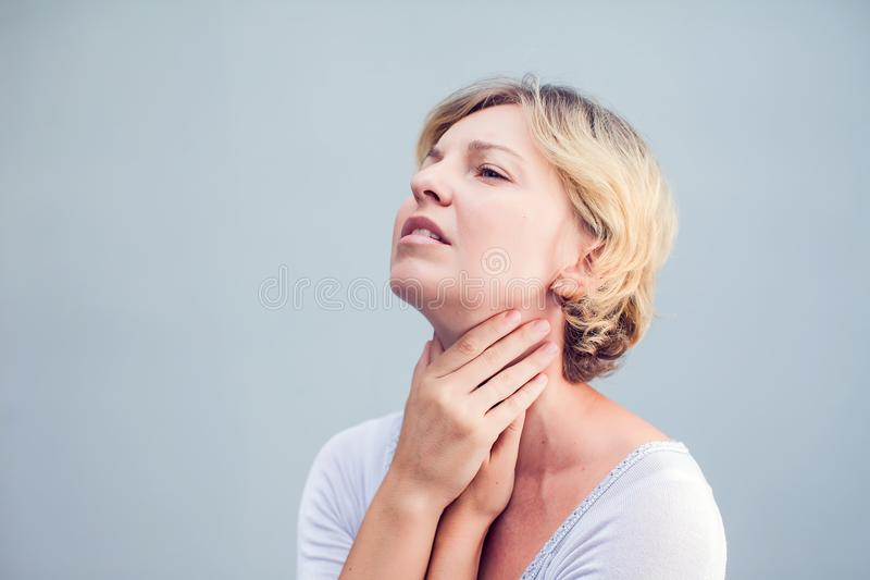 Throat Pain. Closeup Of Sick Woman With Sore Throat Feeling Bad, Suffering From Painful Swallowing. Beautiful Girl Touching Neck. With Hand. Illness, Health royalty free stock photo