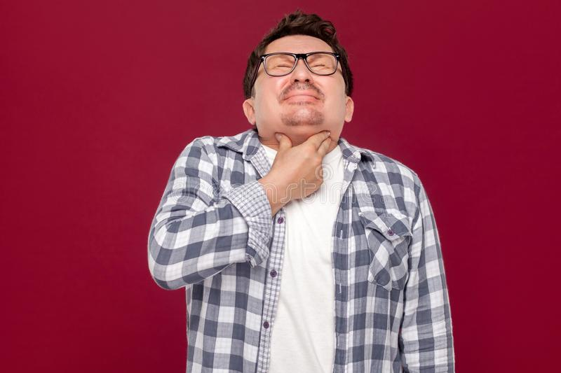 Throat pain on cold. Portrait of middle aged man in casual checkered shirt and eyeglasses standing and holding his painful neck. Because his sick. indoor studio royalty free stock images