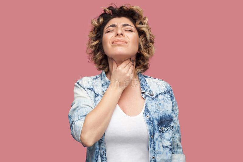 Throat pain or cold. Portrait of young woman with curly hairstyle in casual blue shirt standing and holding her painful neck. Throat pain or cold. Portrait of stock photos