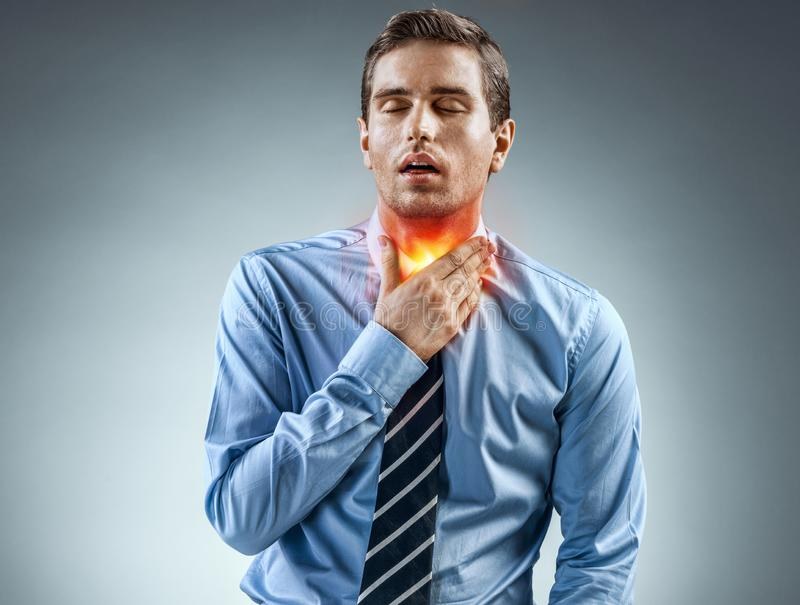 Throat Pain. Office worker holding his inflamed throat. royalty free stock photos