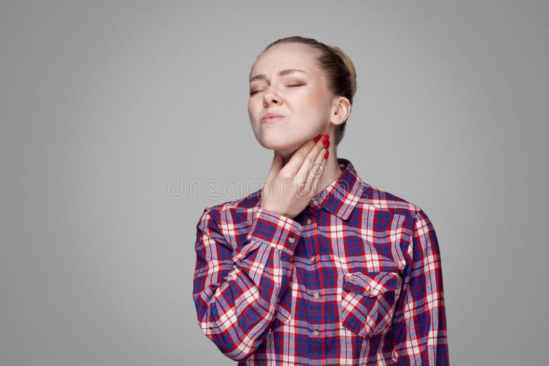 Throat pain. sick blonde girl in red, pink checkered shirt, collected bun hairstyle, makeup standing and touching her painful neck stock image