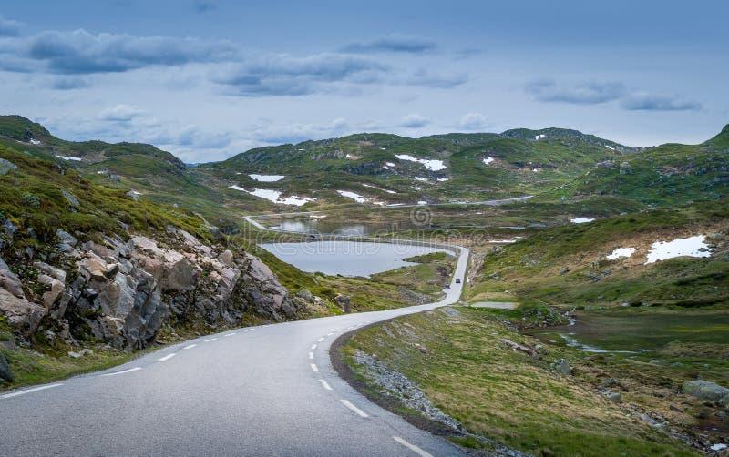 Throgh noruego escénico del camino los lagos y las rocas con algo de nieve imagenes de archivo