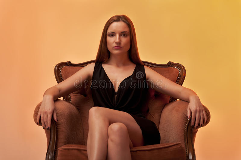 On a throne. Woman sitting on a chair in the evening gown and in brown tones stock photos