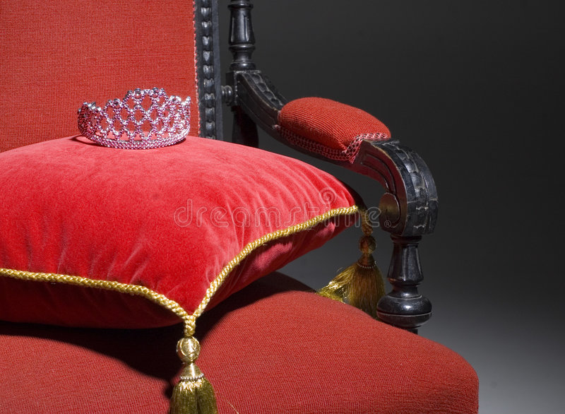 Throne of Importance. Metaphorical scene of a luxurious throne waiting for a queen or princess or miss. Dark background. Armchair with a pillow and crown stock image
