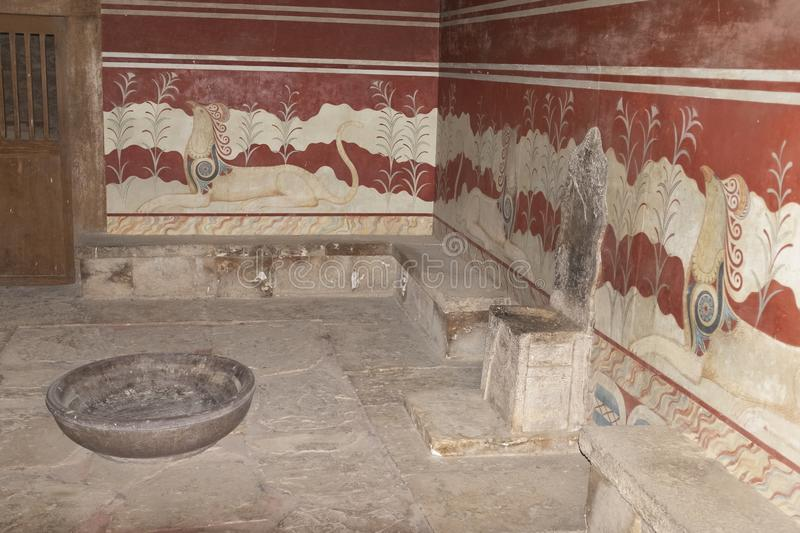 The throne room at the palace of Knossos, Crete. The throne room gets it`s name from the stone seat replicated in wood here found in the room behind this royalty free stock photo