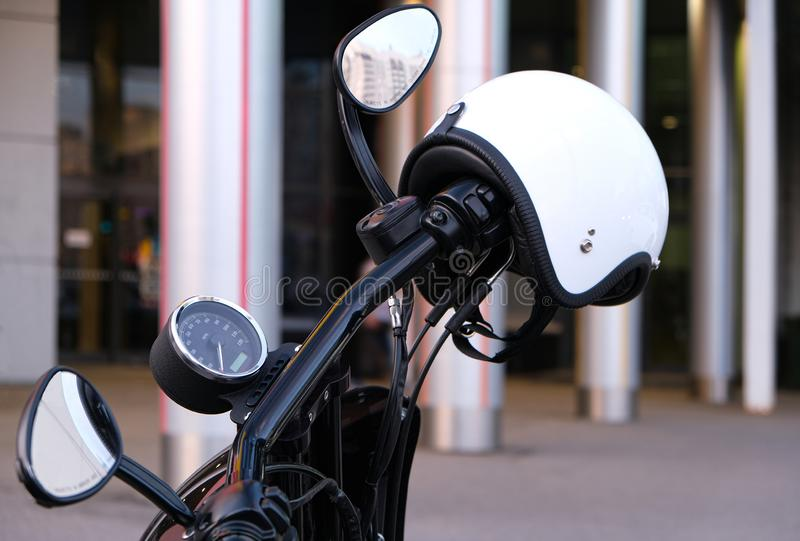 The throttle and brake on the handlebars of the motorcycle with chrome and white helmet without a visor. A white helmet hanging on stock image