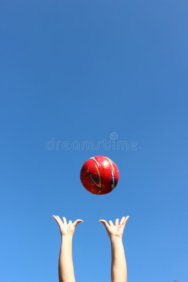 Throuwn vermelho da bola no ar fotografia de stock royalty free