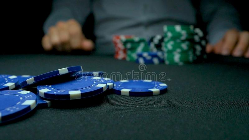 Throw the blue chips in poker. Blue and Red Playing Poker Chips in Reflective black Background. Closeup of poker chips royalty free stock images