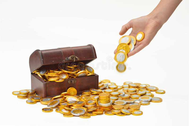 Throw coins. Hand drops money on a heap of chocolate candy euro coins, a treasure chest in the background stock photography
