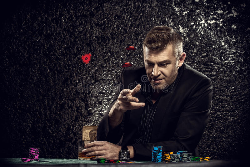 Throwing chips. Excited gambling man throwing chips on a game table in a casino. Gambling, playing cards and roulette royalty free stock photo