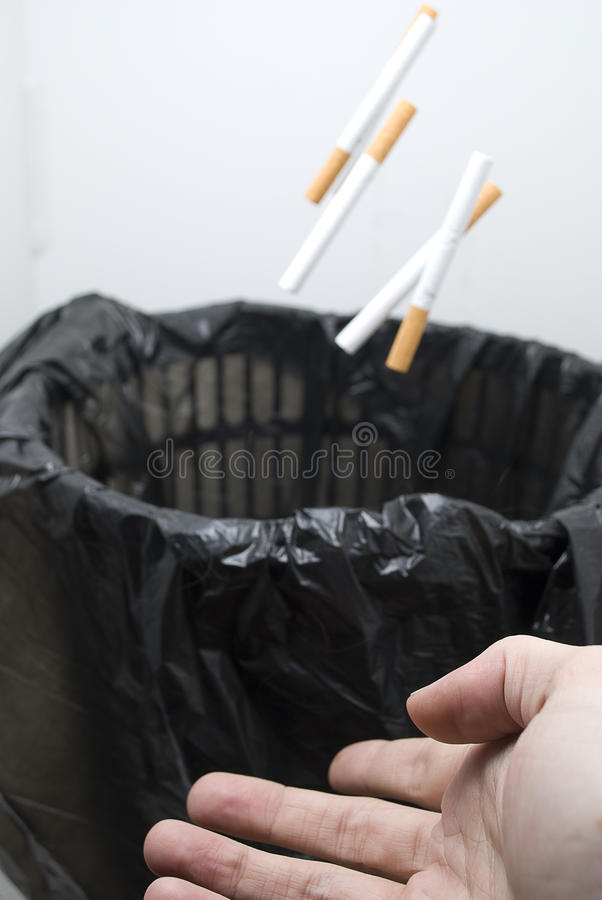 Throwing cigarettes in a bin royalty free stock photos