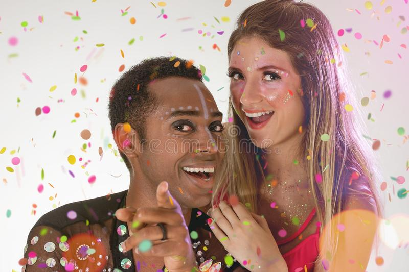 Throwing confetti. Face of brazilian blonde woman and black man wearing carnival costume. Bright and Colorful. Holiday concept, royalty free stock images