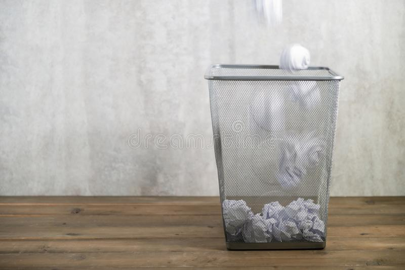 Throwing crumpled paper into trash. Throwing crumpled paper into metal trashcan, waste and save environmental concept royalty free stock photography