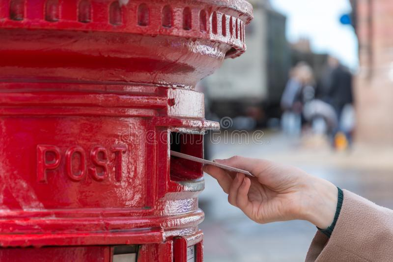 Throwing a letter in a red British post box royalty free stock images