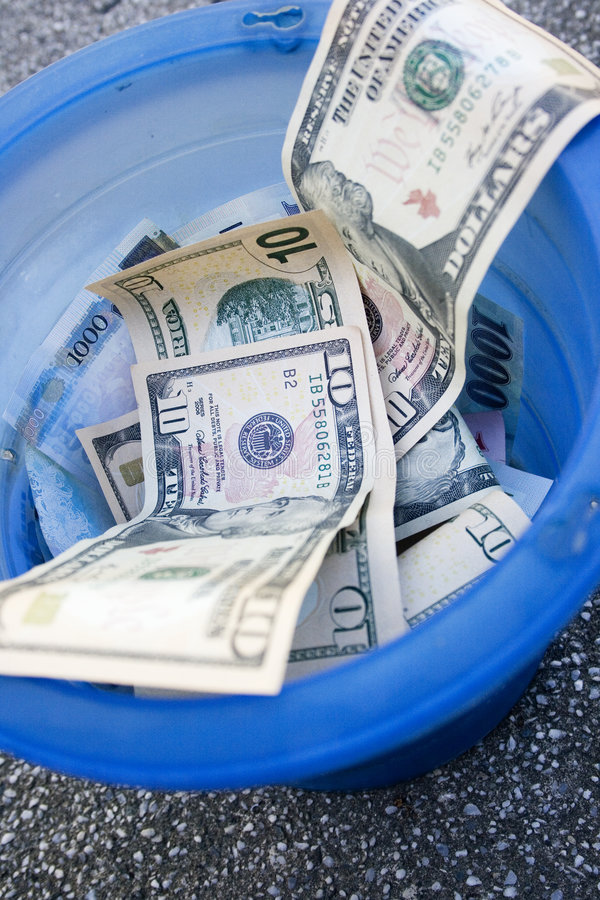 Throwing money away. 10 dollar bills and other money thrown into a trash can royalty free stock photos