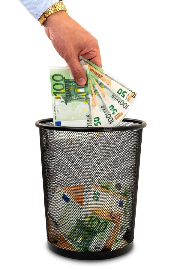 Throwing money away into the trash stock photo