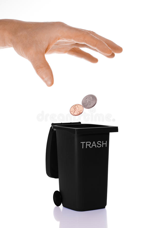 Throwing Money Away. Image showing a male hand dropping / tossing U.S. change, a penny and quarter, into a miniature black trash can stock image