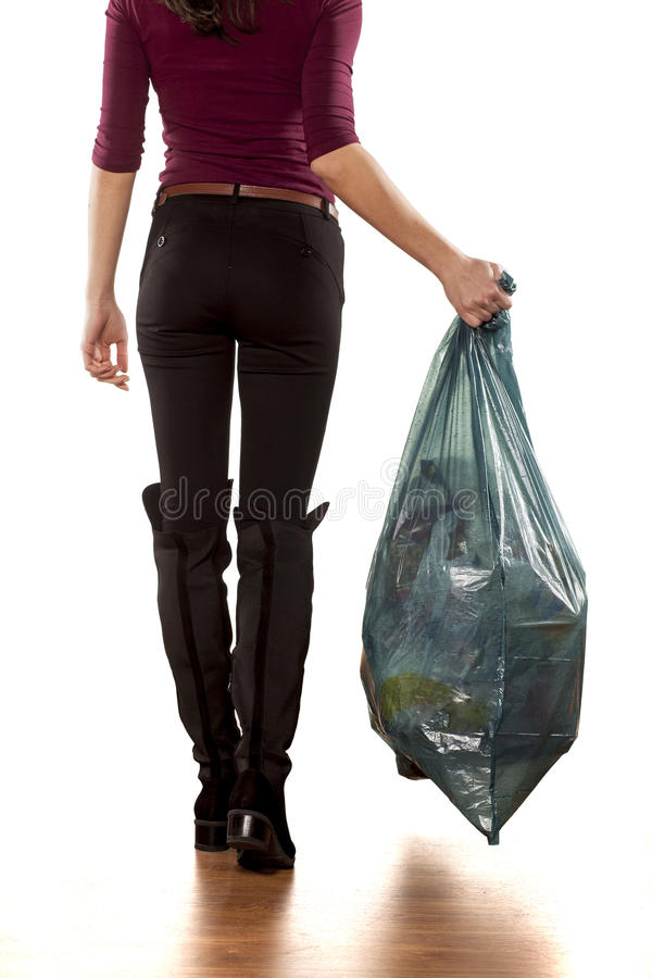 Throwing out the garbage. Back view of a woman holding garbage bag and leaving stock image