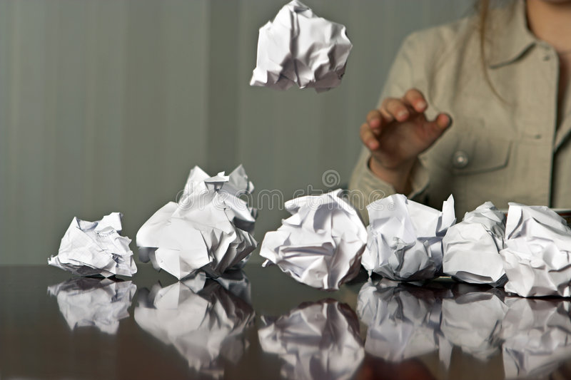 Throwing paper balls. Woman throwing waste paper balls on the table stock photography