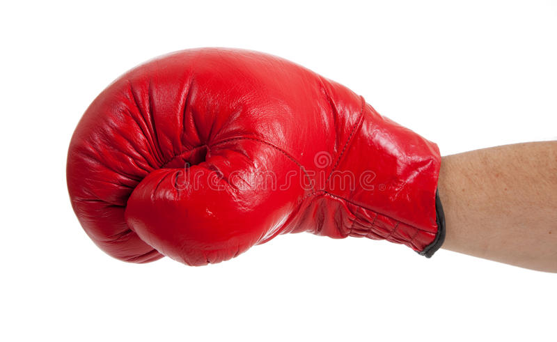Throwing a punch!. A close-up of a persons arm throwing a punch with a red boxing glove on a white background stock photography